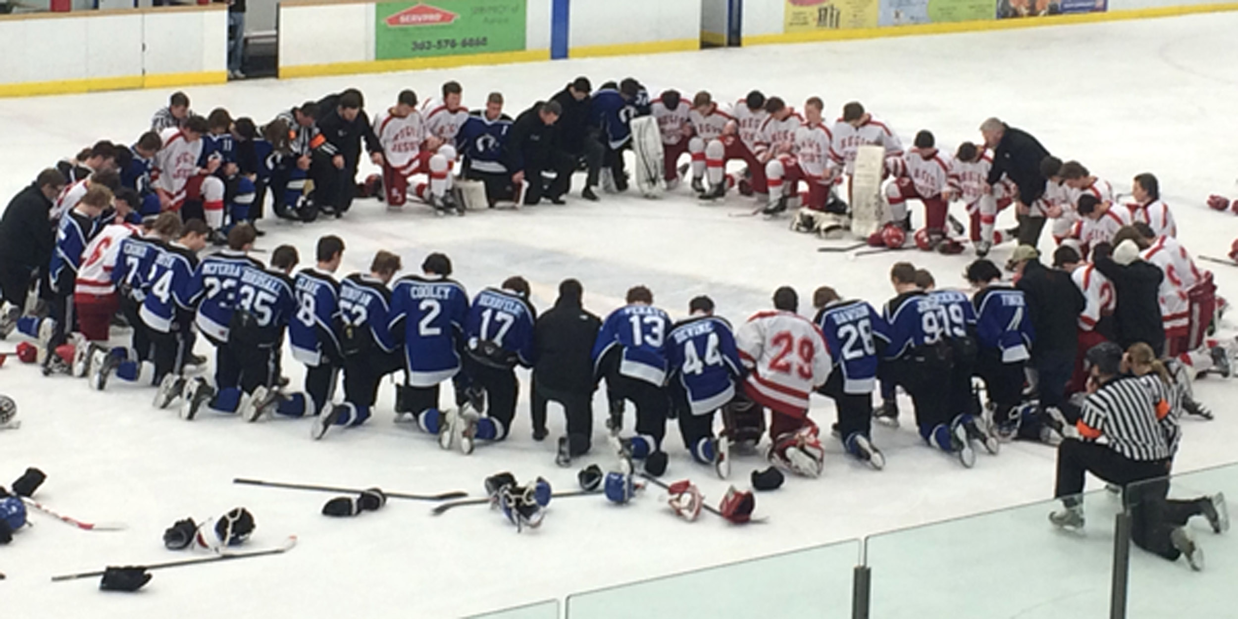 RCS and Regis Jesuit take a moment to pray following the 2015 postseason contest